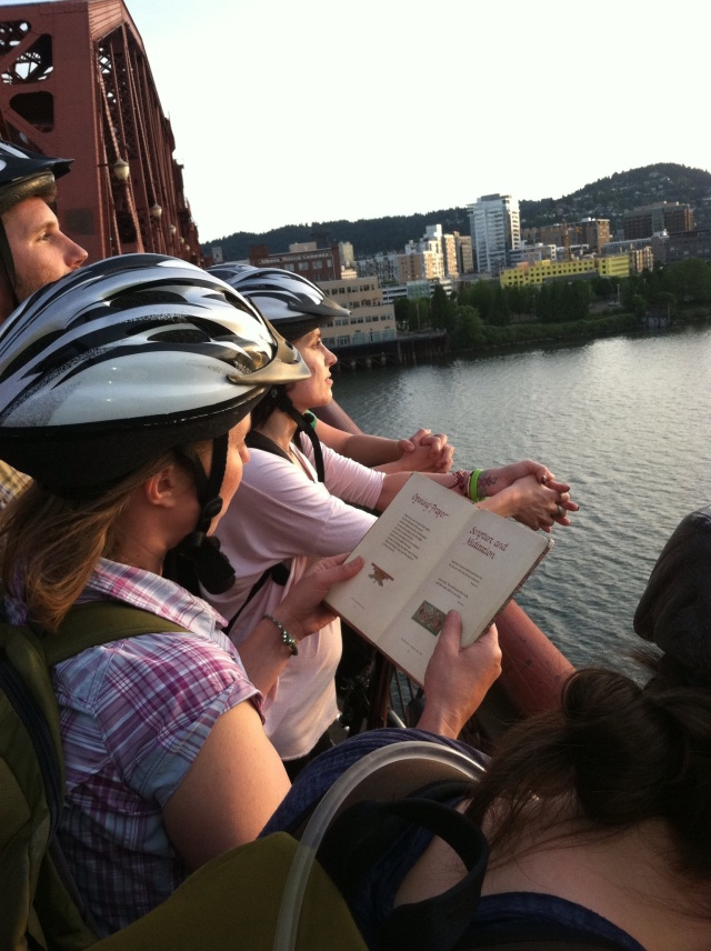 The biking Eco-Stewards Portland team stops for a sunset prayer on the Willamette River.